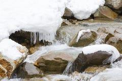 Χιόνι, παγάκια και νερό που ορμούν πέρα από τους βράχους Στοκ εικόνα με δικαίωμα ελεύθερης χρήσης