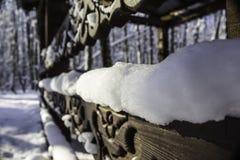 Χιόνι που βρίσκεται σε έναν χαρασμένο ξύλινο πίνακα μετά από χιονοπτώσεις Λεπτομέρεια ενός gazebo στο πάρκο Στοκ Φωτογραφίες