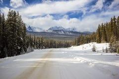 Χιόνι στο μικρό στενό και θυελλώδη δρόμο βουνών μέσω του δάσους με τις υψηλές αιχμές πίσω, εθνικό πάρκο Banff, Καναδάς Στοκ Εικόνες