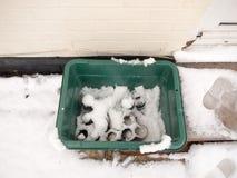 χιόνι στο πράσινο δοχείο πλαστικών κιβωτίων έξω από την ανακύκλωση στοκ φωτογραφία