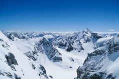 Χιόνι υψηλών βουνών στο χειμερινό blusky υπόβαθρο Στοκ φωτογραφία με δικαίωμα ελεύθερης χρήσης