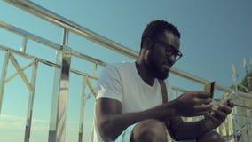 Χιλιετής τύπος που ψωνίζει on-line με το smartphone υπαίθρια φιλμ μικρού μήκους
