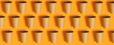 Χλεύη επάνω με το διάστημα αντιγράφων Φλυτζάνια εγγράφου στο πορτοκαλί υπόβαθρο με το διάστημα αντιγράφων στοκ φωτογραφία