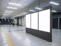 Χλεύη επάνω στο κενό MEDIA εμβλημάτων που διαφημίζει στο σταθμό μετρό με το περπάτημα ανθρώπων κυλιόμενων σκαλών στοκ φωτογραφία με δικαίωμα ελεύθερης χρήσης