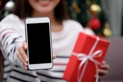 Χλεύη επάνω στο τηλέφωνο, γυναίκα που χαμογελά κρατώντας το έξυπνο τηλέφωνο με blan Στοκ φωτογραφίες με δικαίωμα ελεύθερης χρήσης