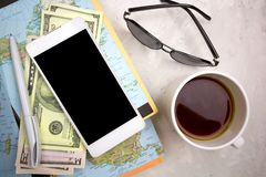 Χλεύη συσκευών επάνω στην οθόνη, τον καφέ, τους χάρτες και τα γυαλιά ηλίου στον πίνακα Στοκ Φωτογραφίες