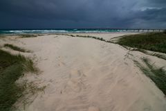 Χλοώδεις παραλία-δευτερεύοντες αμμόλοφοι άμμου με τα σκοτεινά σύννεφα θύελλας στον ορίζοντα στοκ φωτογραφίες