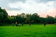 Χλοώδες πάρκο με τους ανθρώπους που περιπλανώνται γύρω σε ένα βράδυ μουσώνα στοκ φωτογραφίες με δικαίωμα ελεύθερης χρήσης