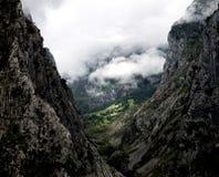 Χλοώδες LIT τομέων μεταξύ δύο νεφελωδών βουνών στοκ φωτογραφία με δικαίωμα ελεύθερης χρήσης