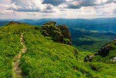 Χλοώδης βουνοπλαγιά πέρα από τον απότομο βράχο στα βουνά στοκ φωτογραφία