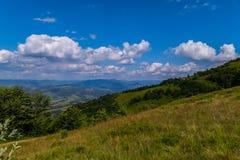 Χλοώδης κάθοδος κλίσης, που αγνοεί την επαρχία των βουνών και των λόφων κάτω από το μπλε ουρανό στοκ εικόνες