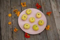 Χλωμιάστε - κίτρινα σύκα σε ένα ρόδινο πιάτο με τα λουλούδια στοκ εικόνες