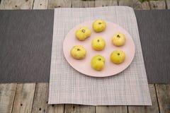 Χλωμιάστε - κίτρινα σύκα σε ένα ρόδινο πιάτο σε μια ξύλινη επιτραπέζια κορυφή στοκ εικόνες