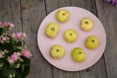 Χλωμιάστε - κίτρινα σύκα σε ένα ρόδινο πιάτο στοκ εικόνες