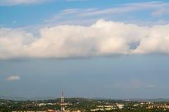 Χνουδωτά σύννεφα πέρα από την πόλη το απόγευμα στοκ εικόνες