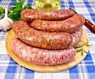 Χοιρινό κρέας και βόειο κρέας λουκάνικων στο μπλε ύφασμα Στοκ Εικόνες