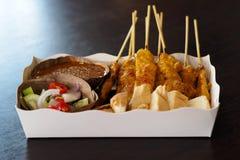 Χοιρινό κρέας Satay με τη σάλτσα φυστικιών και σαλάτα αγγουριών στο δίσκο τροφίμων εγγράφου Στοκ φωτογραφίες με δικαίωμα ελεύθερης χρήσης