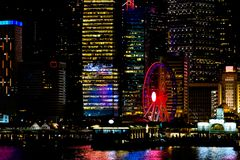 Χονγκ Κονγκ τη νύχτα Η κεντρική αποβάθρα, ferris κυλά, ζωηρόχρωμη διαφήμιση, κινεζικά ιδεογράμματα, όμορφες αντανακλάσεις στοκ εικόνα