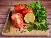 Χονδροειδές άλας πιπεριών μαϊντανού λεμονιών ντοματών φρέσκων λαχανικών και ένα μαχαίρι σε έναν τέμνοντα πίνακα Στοκ Φωτογραφία