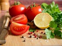 Χονδροειδές άλας πιπεριών μαϊντανού λεμονιών ντοματών φρέσκων λαχανικών και ένα μαχαίρι σε έναν τέμνοντα πίνακα Στοκ εικόνα με δικαίωμα ελεύθερης χρήσης