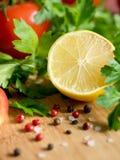 Χονδροειδές άλας πιπεριών μαϊντανού λεμονιών ντοματών φρέσκων λαχανικών σε έναν τέμνοντα πίνακα Στοκ Φωτογραφία