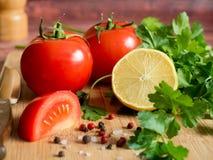 Χονδροειδές άλας πιπεριών μαϊντανού λεμονιών ντοματών φρέσκων λαχανικών σε έναν τέμνοντα πίνακα Στοκ Εικόνες