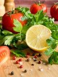 Χονδροειδές άλας πιπεριών μαϊντανού λεμονιών ντοματών φρέσκων λαχανικών σε έναν τέμνοντα πίνακα Στοκ Εικόνα