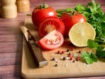 Χονδροειδές άλας πιπεριών μαϊντανού λεμονιών ντοματών φρέσκων λαχανικών και ένα μαχαίρι σε έναν τέμνοντα πίνακα Στοκ φωτογραφία με δικαίωμα ελεύθερης χρήσης