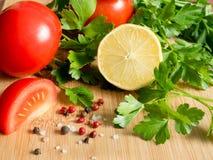Χονδροειδές άλας πιπεριών μαϊντανού λεμονιών ντοματών φρέσκων λαχανικών σε έναν τέμνοντα πίνακα Στοκ φωτογραφία με δικαίωμα ελεύθερης χρήσης