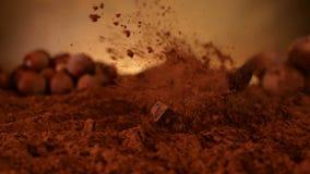 Χοντρά κομμάτια σοκολάτας που περιέρχονται στο ράντισμα κακάου - σε αργή κίνηση φιλμ μικρού μήκους