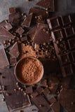 Χοντρά κομμάτια σοκολάτας και σκόνη κακάου Κομμάτια φραγμών σοκολάτας φασολιών καφέ Μεγάλος φραγμός της σοκολάτας στο γκρίζο αφηρ Στοκ Φωτογραφίες