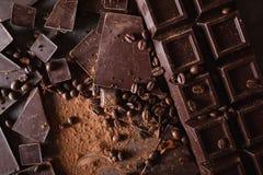Χοντρά κομμάτια σοκολάτας και σκόνη κακάου Κομμάτια φραγμών σοκολάτας φασολιών καφέ Μεγάλος φραγμός της σοκολάτας στο γκρίζο αφηρ Στοκ φωτογραφία με δικαίωμα ελεύθερης χρήσης