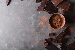 Χοντρά κομμάτια σοκολάτας και σκόνη κακάου Κομμάτια φραγμών σοκολάτας Ένας μεγάλος φραγμός της σοκολάτας στο γκρίζο αφηρημένο υπό Στοκ Φωτογραφίες
