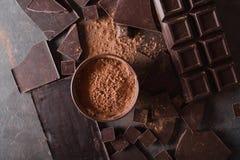 Χοντρά κομμάτια σοκολάτας και σκόνη κακάου Κομμάτια φραγμών σοκολάτας Ένας μεγάλος φραγμός της σοκολάτας στο γκρίζο αφηρημένο υπό Στοκ εικόνες με δικαίωμα ελεύθερης χρήσης
