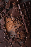 Χοντρά κομμάτια σοκολάτας και σκόνη κακάου Κομμάτια φραγμών σοκολάτας Ένας μεγάλος φραγμός της σοκολάτας στο γκρίζο αφηρημένο υπό Στοκ Εικόνες