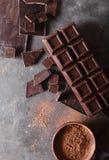 Χοντρά κομμάτια σοκολάτας και σκόνη κακάου Κομμάτια φραγμών σοκολάτας Ένας μεγάλος φραγμός της σοκολάτας στο γκρίζο αφηρημένο υπό Στοκ Φωτογραφία