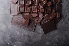 Χοντρά κομμάτια σοκολάτας Κομμάτια φραγμών σοκολάτας Ένας μεγάλος φραγμός της σοκολάτας στο γκρίζο αφηρημένο υπόβαθρο Γ Στοκ εικόνα με δικαίωμα ελεύθερης χρήσης