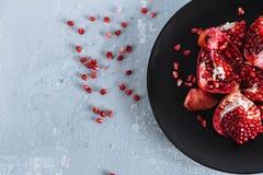 Χοντρά κομμάτια του ώριμου κόκκινου ροδιού στο μαύρο πιάτο με το λευκό στο ανοικτό γκρι, ανώμαλο υπόβαθρο, κινηματογράφηση σε πρώ στοκ εικόνα