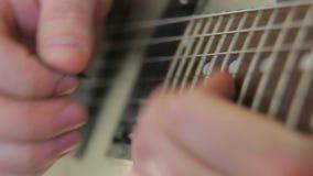 Χορδές επιλογών δάχτυλων κινηματογραφήσεων σε πρώτο πλάνο στην κιθάρα απόθεμα βίντεο