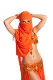 Χορευτής κοιλιών που κρυφοκοιτάζει από πίσω από ένα φωτεινό πορτοκαλί πέπλο Στοκ Φωτογραφίες
