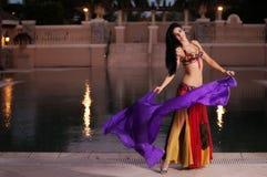 Χορευτής κοιλιών στους κόκκινους χορούς κοστουμιών με το πορφυρό πέπλο στοκ φωτογραφίες με δικαίωμα ελεύθερης χρήσης