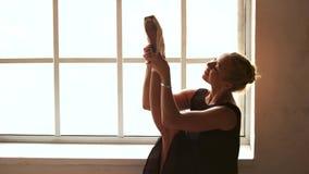 Χορευτής μπαλέτου που τεντώνει το πόδι της στο στούντιο απόθεμα βίντεο