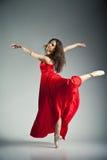 Χορευτής μπαλέτου που φορά το κόκκινο φόρεμα πέρα από το γκρι στοκ εικόνες με δικαίωμα ελεύθερης χρήσης