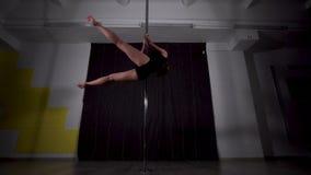 Χορευτής νέων κοριτσιών που χορεύει σε έναν πόλο στο σκοτάδι απόθεμα βίντεο