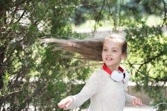 Χορευτής παιδιών με τη μακριά πετώντας τρίχα Χορός παιδιών στη μουσική στο θερινό πάρκο Το μικρό κορίτσι απολαμβάνει τη μουσική σ Στοκ φωτογραφίες με δικαίωμα ελεύθερης χρήσης