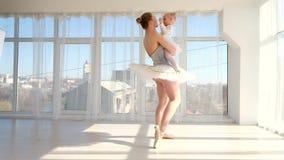 Χορευτής Ballerina που στέκεται tiptoe και που κρατά σε ετοιμότητα την λίγη κόρη απόθεμα βίντεο