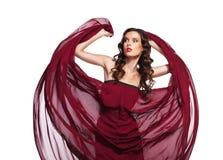 Χορεύοντας γυναίκα στο κόκκινο φόρεμα που πετά στον αέρα στοκ φωτογραφίες