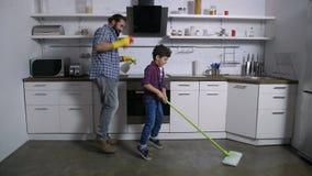 Χορεύοντας ευτυχής οικογένεια που καθαρίζει επάνω το σπίτι από κοινού απόθεμα βίντεο