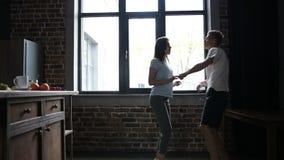 Χορεύοντας ζεύγος που έχει τη διασκέδαση στη σύγχρονη κουζίνα απόθεμα βίντεο