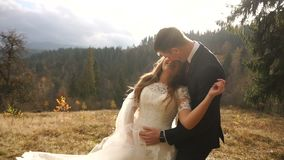 Χορεύοντας ζεύγος των newlyweds ερωτευμένων στα γοητευτικά χρυσά βουνά Ευτυχείς γαμήλιες στιγμές απόθεμα βίντεο